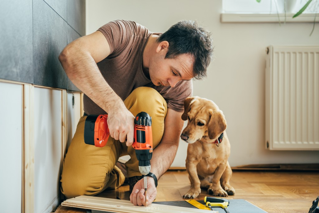 Drilling a plank of wood with dog beside him