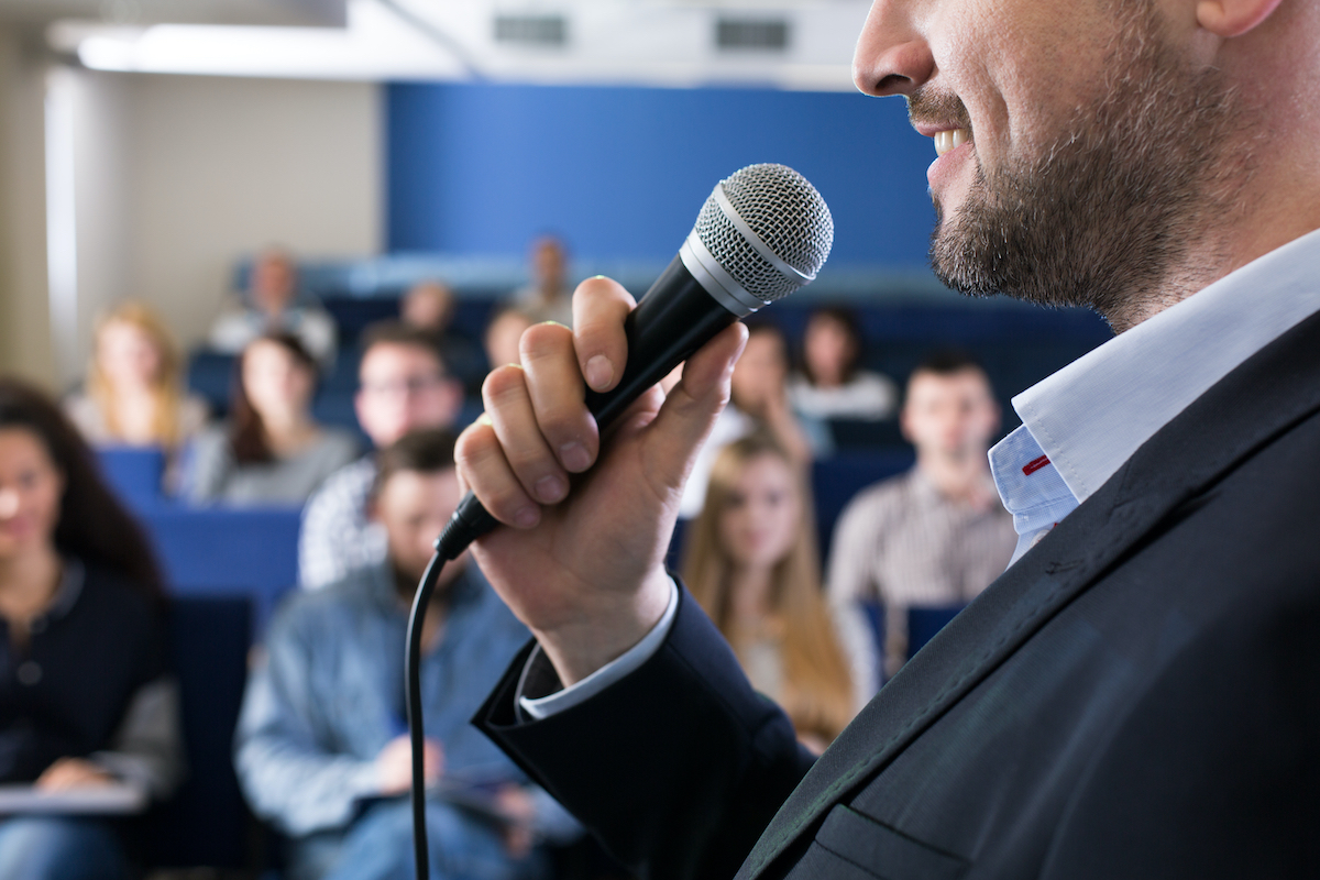 man giving a speech in front of an audience
