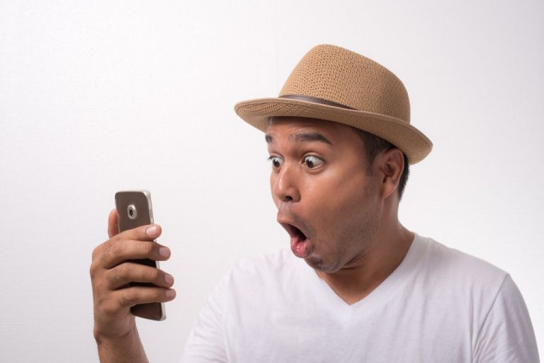 man shocked looking at his phone
