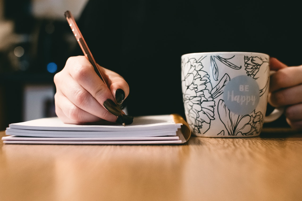 writing on notebook while holding a cup of coffee