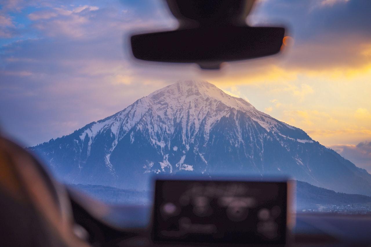 person driving towards a mountain