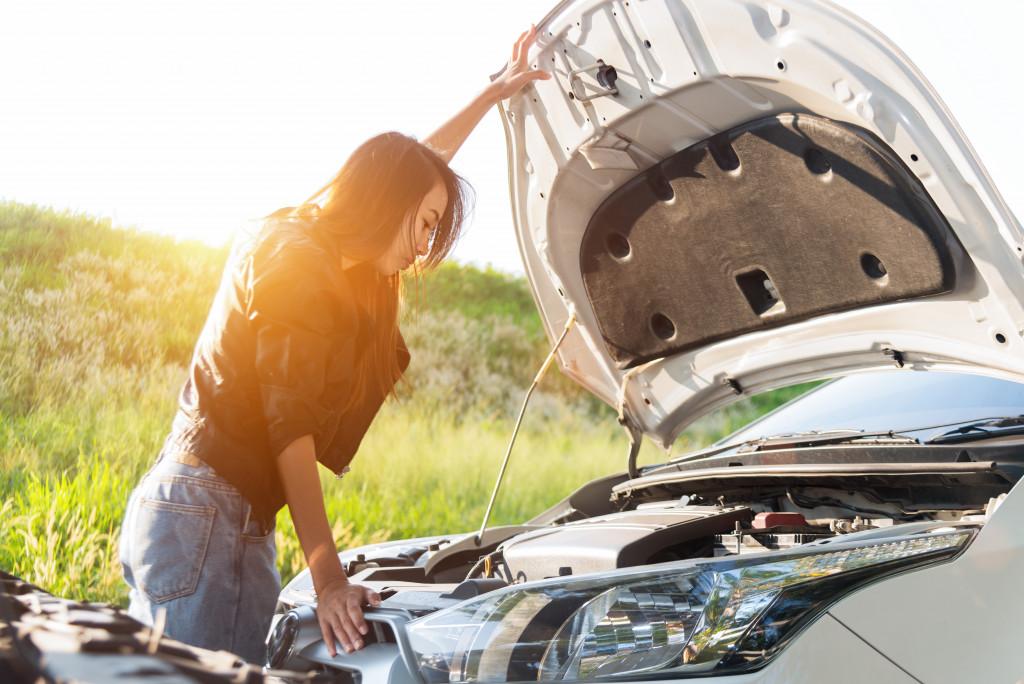 woman fixing car engine