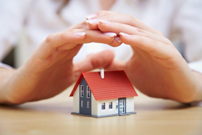 hands hovering over miniature house model